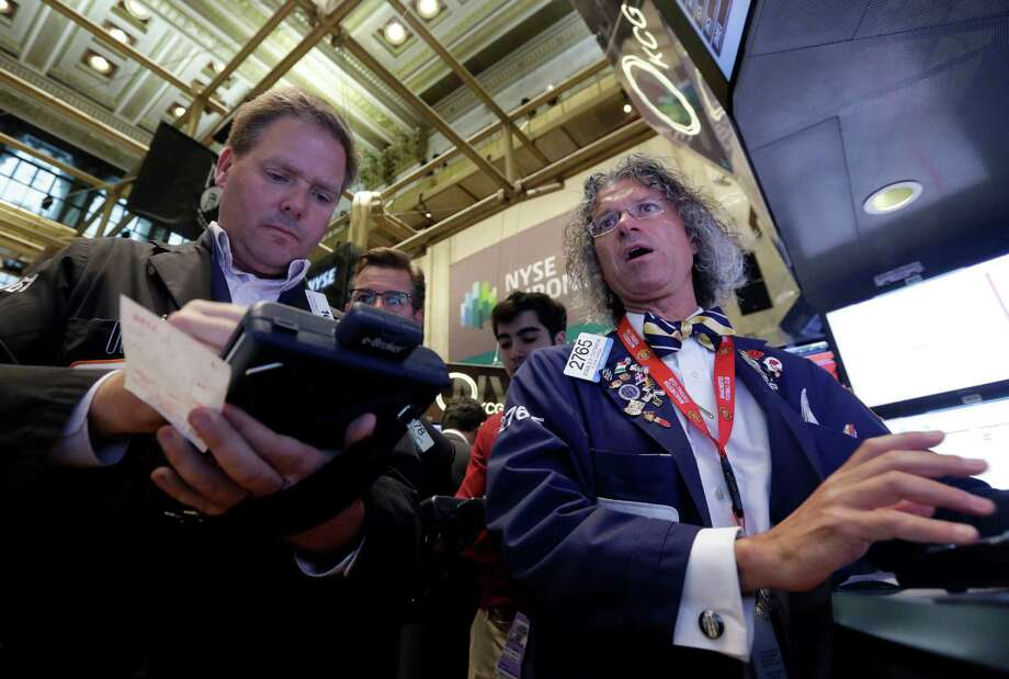 Trader Thomas McCauley, left, and specialist Donald Civitanova work on the floor of the New York Stock Exchange, Friday, May 23, 2014. Stocks inched higher early Friday in quiet trading ahead of the Memorial Day weekend.  (AP Photo/Richard Drew)  ORG XMIT: NYRD102 Photo: Richard Drew / AP