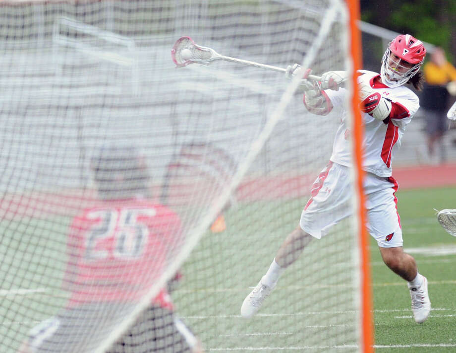 At right, Kyle Foote of Greenwich shoots as Fairfield Warde goalie Jason Nerreau defends on a shot that went high during the FCIAC boys high school lacrosse quarterfinal match between Greenwich High School and Fairfield Warde High School at Greenwich, Friday night, May 23, 2014. Photo: Bob Luckey / Greenwich Time