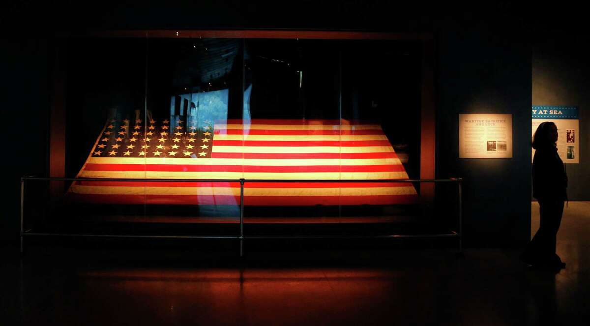 A security guard stands next to the historic American flag that flew over the Battleship Texas at D-Day on public display for first time at the Museum of Natural Science, Friday, May 23, 2014, in Houston.