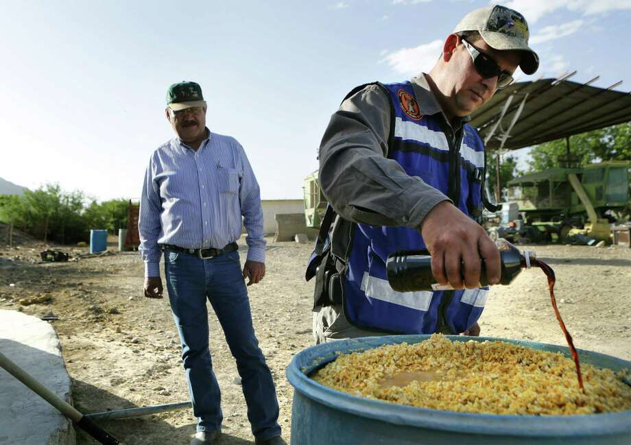 Leonel Duran, right, an exotic animal control agent for the State of Chihuahua, pours a bottle of vanilla extract into a barrel of fermented corn to be used as bait in a trap for feral hogs on a farm just outside Ojinaga, MX.  Tuesday, May 13, 2014.  At left is Luis Antonio Gamboa Ballesteros, Chief of the Wildlife Department for the State of Chihuahua. Photo: BOB OWEN, San Antonio Express-News / © 2012 San Antonio Express-News