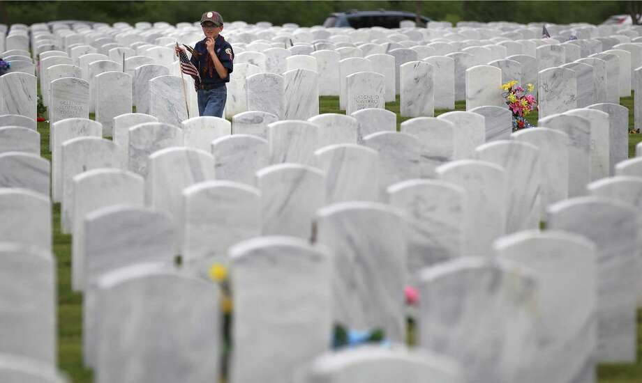 """C.J. Ruvalcaba, 9, of Cub Scout Pack 93 carries flags to place beside headstones at Fort Sam Houston National Cemetery on Friday, May 23, 2014. Over 2,000 people mostly members of the Alamo Area Council of Boy Scouts of America paid homage to the military service personnel that were laid to rest at the cemetery. Over 100,000 flags were distributed and placed beside headstones in advance of the Memorial Day observance. """"This is a great way for our children to learn about citizenship,"""" said Renee Greer, Assistant Scout Master with Troop 398, who helped coordinated the event. Photo: Kin Man Hui, San Antonio Express-News / ©2014 San Antonio Express-News"""
