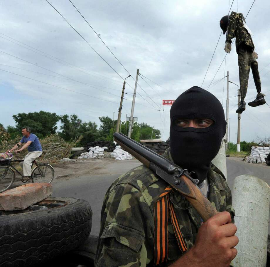 On the eve of the Ukrainian presidential election, a pro-Russian gunman guards a checkpoint near the eastern city of Slavyansk. Behind and above him, a Ukrainian hangs in effigy. Photo: Victor Drachev / AFP / Getty Images / AFP