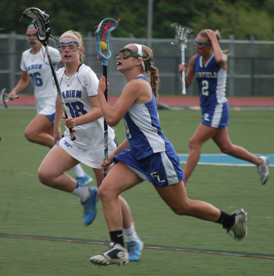 Fairfield Ludlowe's Emily Demaso carries the ball as Darien's Kellyn Berrigan gives chase in an FCIAC girls lacrosse quarterfinal on Friday, May 23 at Darien. The Blue Wave won 19-6. Photo: Andy Hutchison / Fairfield Citizen