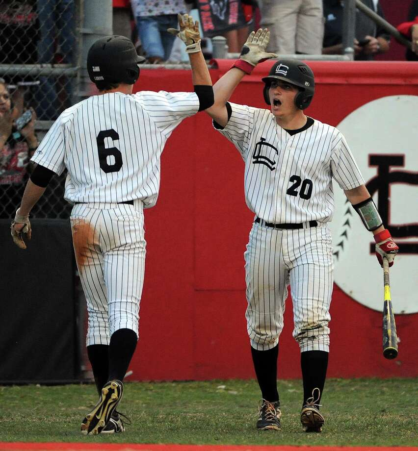 Langham Creek's Kyle Finkenstaedt, left, celebrates his run scored with Michael Hoehner during the second inning of a high school baseball regional semifinal playoff game against Brazoswood, Friday, May 23, 2014, at Langham Creek High School in Cypress. Photo: Eric Christian Smith, For The Chronicle