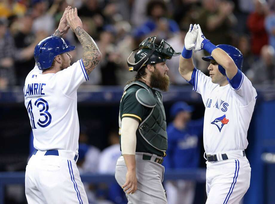 Brett Lawrie (left) greets Steve Tolleson after Tolleson's two-run homer off Scott Kazmir in the second inning. Photo: Frank Gunn, Associated Press