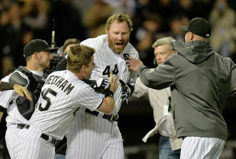 Slugger Adam Dunn (44) is mobbed by Gordon Beckham, left, and other teammates after hitting a walkoff homer to lead the White Sox past the Yankees. Photo: Brian Kersey, Stringer / 2014 Getty Images
