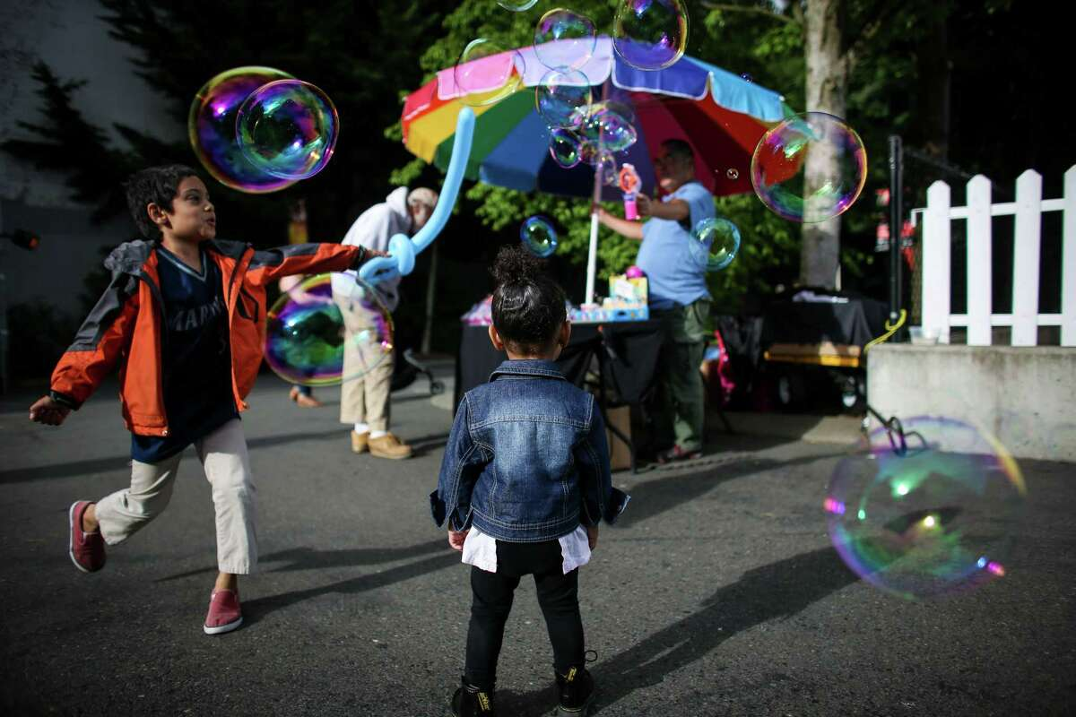 Children try to pop bubbles during the 2014 Northwest Folklife Festival at the Seattle Center. The four day event features cultural performances, lots of food, dancing and of course drum circles. Photographed on Saturday, May 24, 2014.