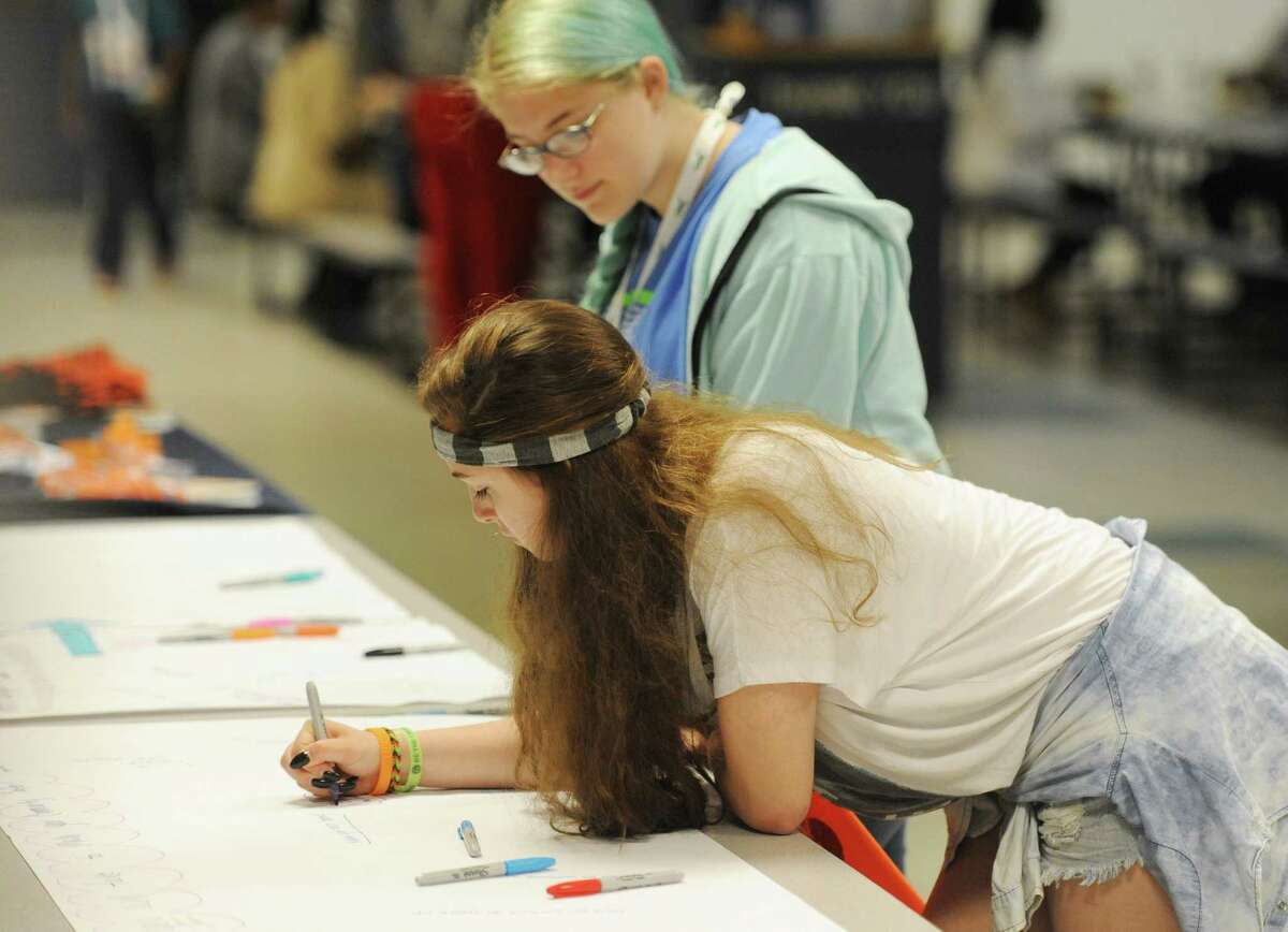 Newtown students Tallie Nikitchyuk, top, 14, and Rebecca Spalvieri, 15, write on a piece of paper asking the questions