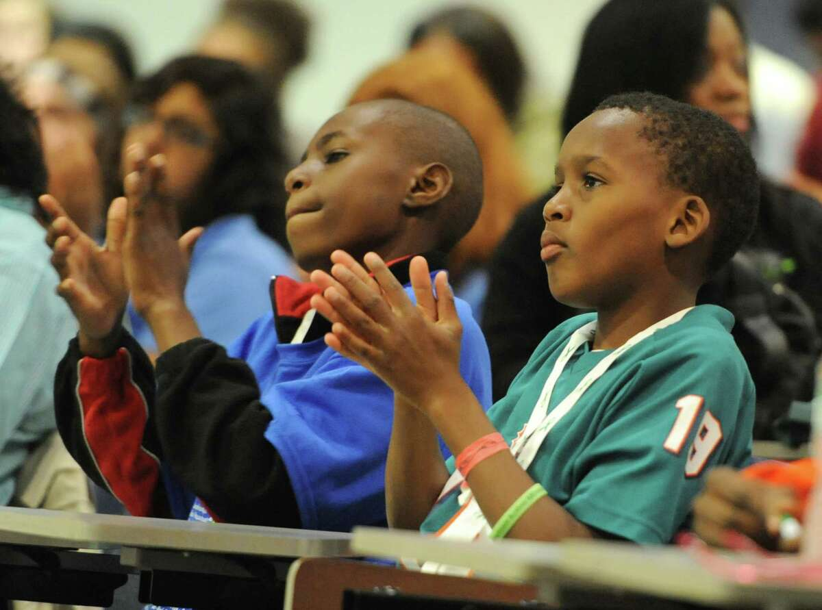 Christpher Anderson, left, 13, of Hartford, and Israel Henriquez, 10, of West Hartford, clap during the Honor With Action Youth Leadership Summit on Gun Violence Prevention at Newtown High School in Newtown, Conn. Saturday, May 24, 2014. The summit featured keynote speaker Ishmael Beah, a Sierra Leonean best-selling author and human rights activist. The event included many large group activities and small workshops such as story exchange, a young activist panel, a movie about Virginia Tech shooting survivor Colin Goddard, healing through the arts, and breakout sessions about spirituality and mental health. About 100 children from across the state and Harlem, N.Y. attended the summit.
