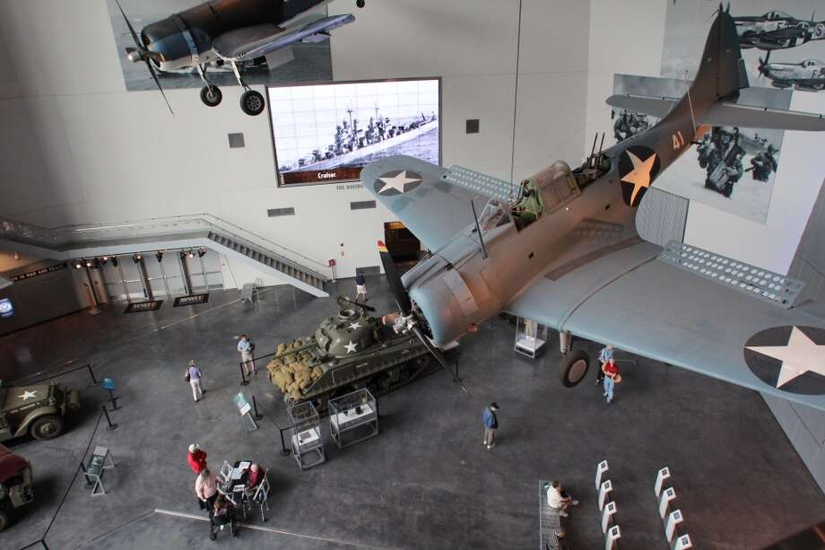 "The Douglas SBD Dauntless ""flies"" over a Sherman Tank in the pavilion. Photo: Spud Hilton, Bad Latitude"
