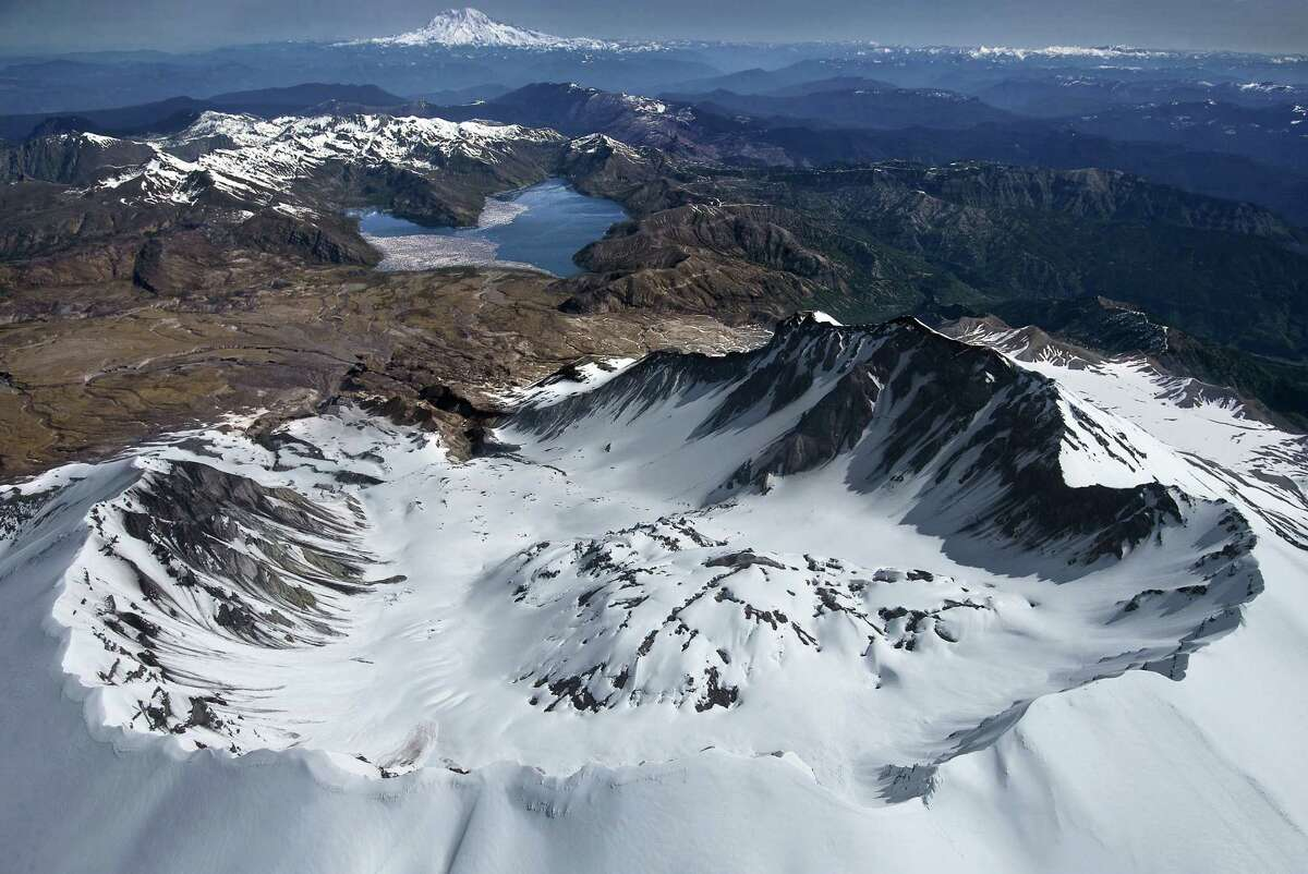 The view of a rim of Mount Saint Helens, looking past a venting lava dome north toward Spirit Lake and Mount Rainier, is awe-inspiring. Scientists are studying a repressurizing of the magma chamber underneath.