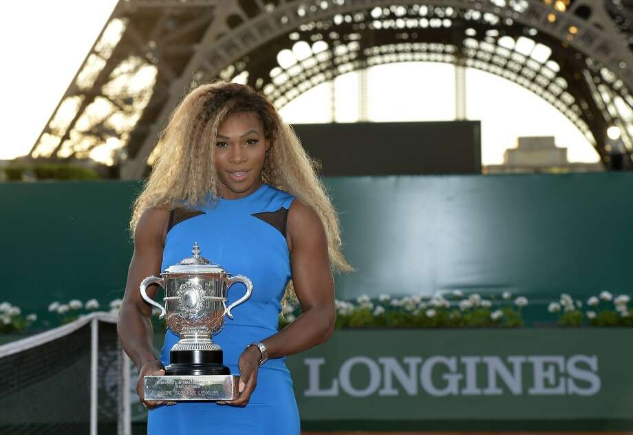 Serena Williams poses with the French Open trophy she won last year while standing in front of the Eiffel Tower in Paris, where she has an apartment. Photo: Miguel Medina, AFP/Getty Images