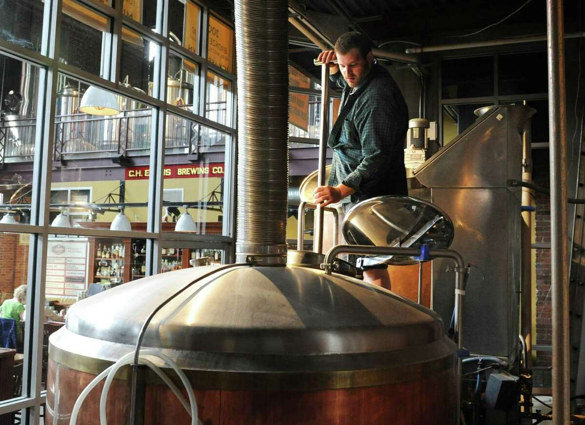 Assistant brewer Sam Pagano demonstrates how to stir the mash with a paddle in a brewery vat that turns grains into beer at the Albany Pump Station on Tuesday, May 13, 2014 in Albany, N.Y. (Lori Van Buren / Times Union)