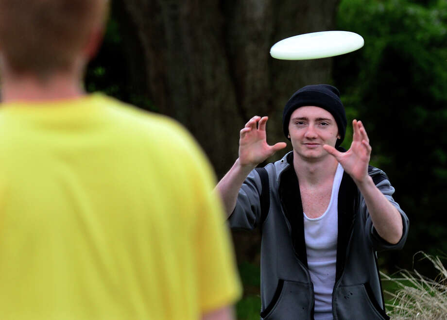 Jesse Montanaro reaches out to catch a frisbee thrown by his friend James Davidson along Oak Bluff Avenue in Stratford, Conn. on Saturday May 24, 2014. Photo: Christian Abraham / Connecticut Post