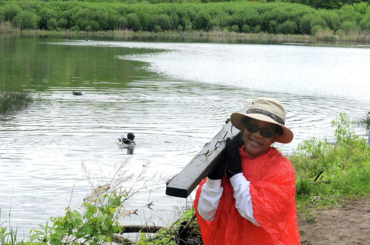 Vilma Elliott a volunteer with Friends of the Woodlawn Preserve carries a piece of wood found by divers looking for debris in the Woodlawn Preserve pond on Saturday May 24, 2014 in Schenectady, N.Y. (Michael P. Farrell/Times Union)