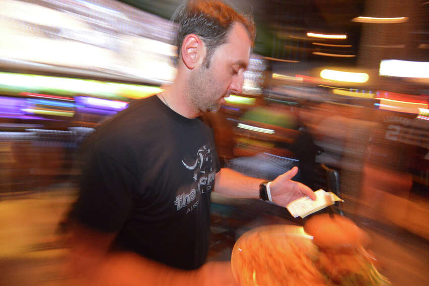 Chip Ingram, owner of the Australian-themed Roo Pub, checks a food order during a crowded night as the Spurs play in Game 2 of the NBA Western Conference Finals against the Thunder.