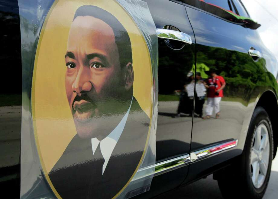 A picture of Martin Luther King Jr. is seen on the side of a car during a parade to MacGregor Park on Saturday, May 24, 2014, in Houston. Photo: J. Patric Schneider, For The Chronicle / © 2014 Houston Chronicle