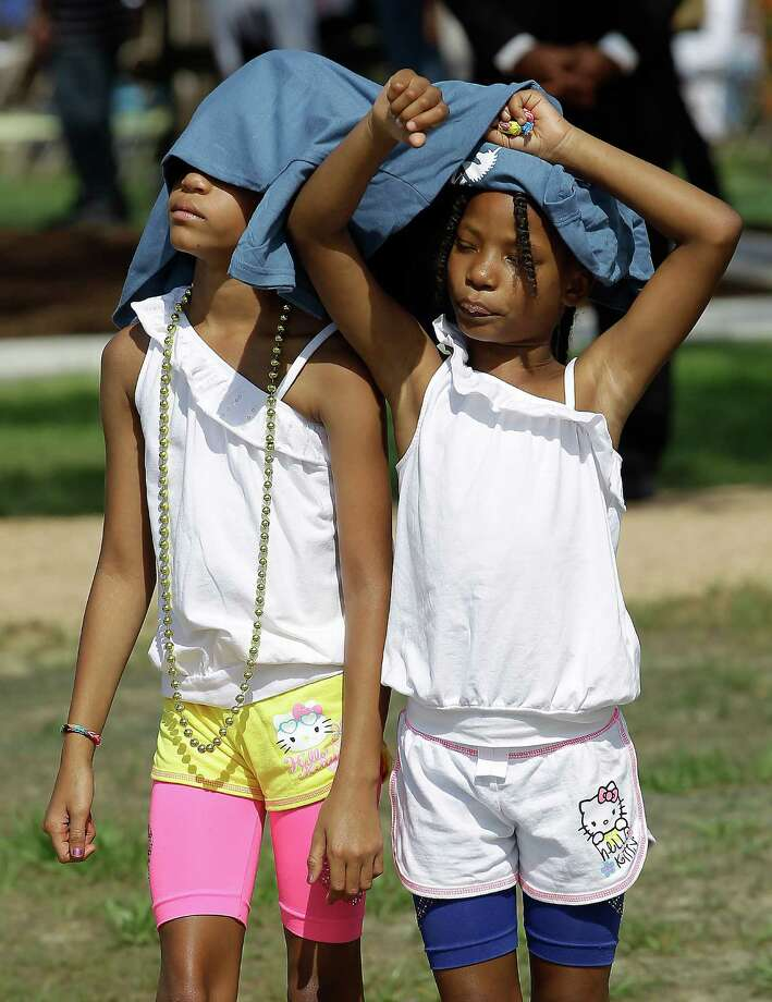 Sisters Jamya, 9, and Jamelah Tompkins, 8, try to beat the heat as the parade marches by to MacGregor Park for the unveiling of the new Martin Luther King Jr. statue on Saturday, May 24, 2014, in Houston. Photo: J. Patric Schneider, For The Chronicle / © 2014 Houston Chronicle