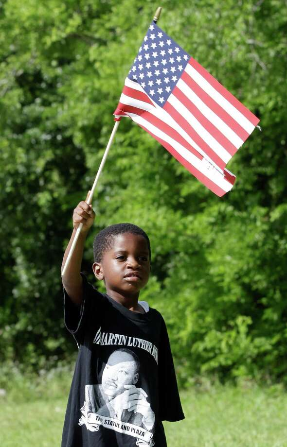 Four-year-old Cedric Washington Jr. waves his American flag as the parade marches by to MacGregor Park for the unveiling of the new Martin Luther King Jr. statue on Saturday, May 24, 2014, in Houston. Photo: J. Patric Schneider, For The Chronicle / © 2014 Houston Chronicle