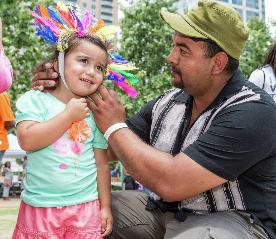 Dad Rey Chavana adjusts a little headdress on 3-year-old Chamila Chavana. Photo: Craig Hartley, For The Chronicle / Copyright: Craig H. Hartley