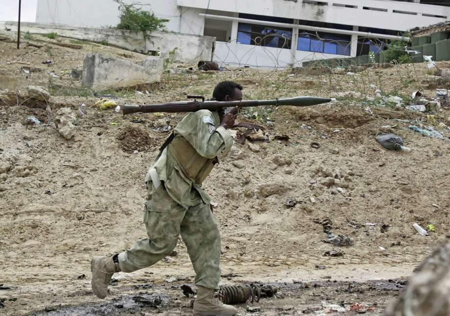 A Somali soldier carrying a rocket launcher runs to fight during an attack on Somalia's parliament in Mogadishu by militants. At least 15 people, most of them assailants, were killed, and more than a dozen guards were wounded, an official said. / AP