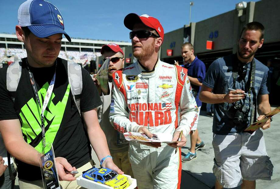 Dale Earnhardt Jr. (center) signs autographs for fans after practice Saturday at Charlotte Motor Speedway. He'll start 10th in the field for the Coca-Cola 600. Photo: Jeff Siner / McClatchy-Tribune News Service / Charlotte Observer