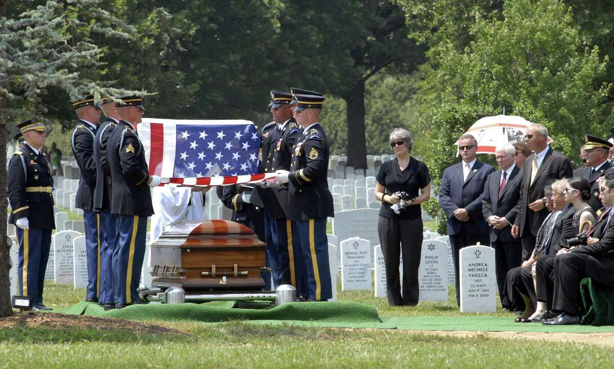 A military honor guard folds the American flag that covered the casket of Pfc. David Taylor Miller as his family and Secretary of Defense Robert Gates observe at Arlington National Cemetery on Wednesday. (Meredith McDermott/ Hearst Newspapers)