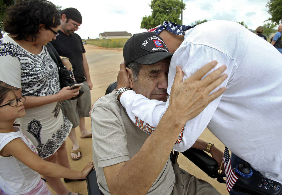 Vietnam War veteran Pablo Duenes gets a hug from Alex Paiz, a veteran of Operation Iraqi Freedom, at the culmination of the motorcycle run at the Frank M. Tejeda Veterans Home in Floresville as Duenes' family looks on. Photo: Photos By Tom Reel / San Antonio Express-News
