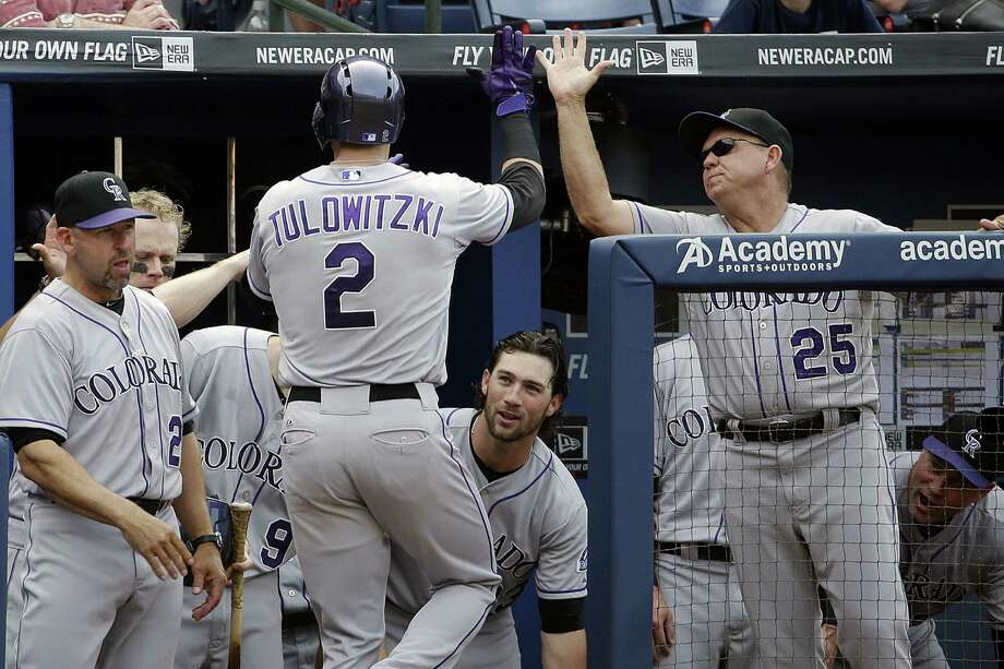 Troy Tulowitzki (center) high-fives his teammates after hitting a home run in the sixth inning. Photo: David Goldman / Associated Press / AP