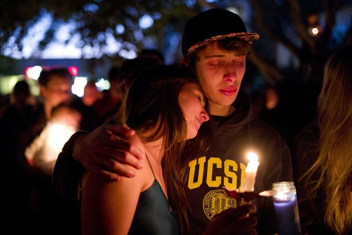 Two students comfort each other during a candlelight vigil held to honor the victims of Friday night's mass shooting on Saturday, May 24, 2014, in Isla Vista, Calif. Sheriff's officials say Elliot Rodger, 22, went on a rampage near the University of California, Santa Barbara, stabbing three people to death at his apartment before shooting and killing three more in a crime spree through a nearby neighborhood. (AP Photo/Jae C. Hong)