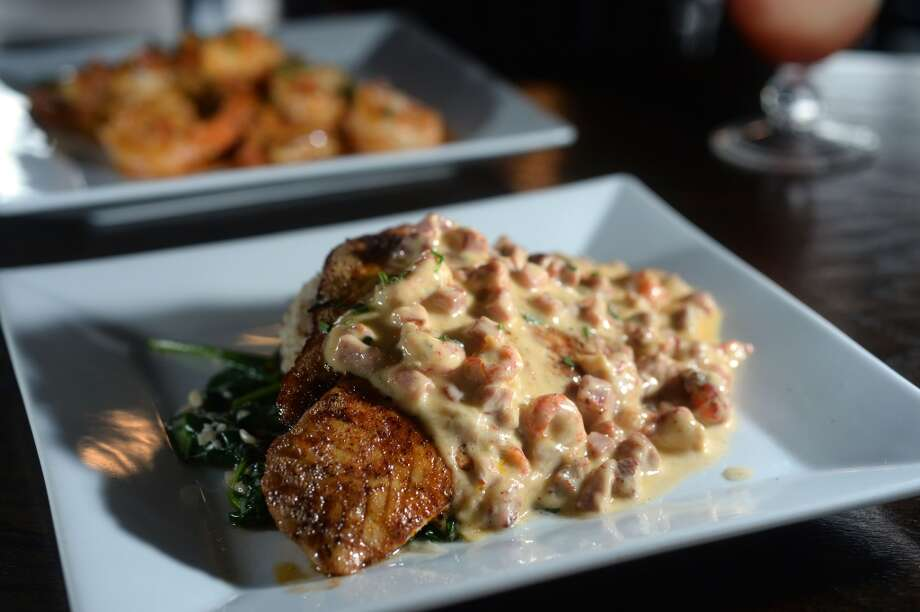 Red fish topped with a crawfish sauce and served with spinach and dirty rice at the Neches River Wheelhouse in Port Neches. Photo taken Tuesday, May 13, 2014 Guiseppe Barranco/@spotnewsshooter