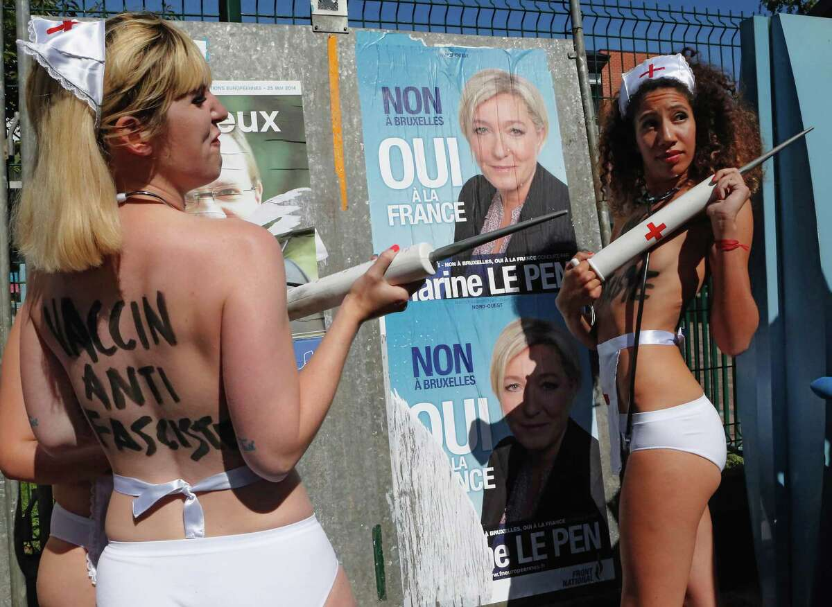 A group of Femen activists, with nurse head pieces, makeshift needles and the words 'Vaccin Anti Fascists' painted on their backs, demonstrate in front of an election poster of French far-right leader Marine Le Pen nearby a polling station in Henin-Beaumont, northern France, Sunday, May 25, 2014. The National Front, which also wants to unravel the European Union and withdraw France from the euro currency, hopes to win up to 20 of France's 74 European Parliament seats in their Sunday vote. It currently holds just two seats, but polls show it running neck-and-neck with the conservative UMP party and well ahead of the governing Socialists.