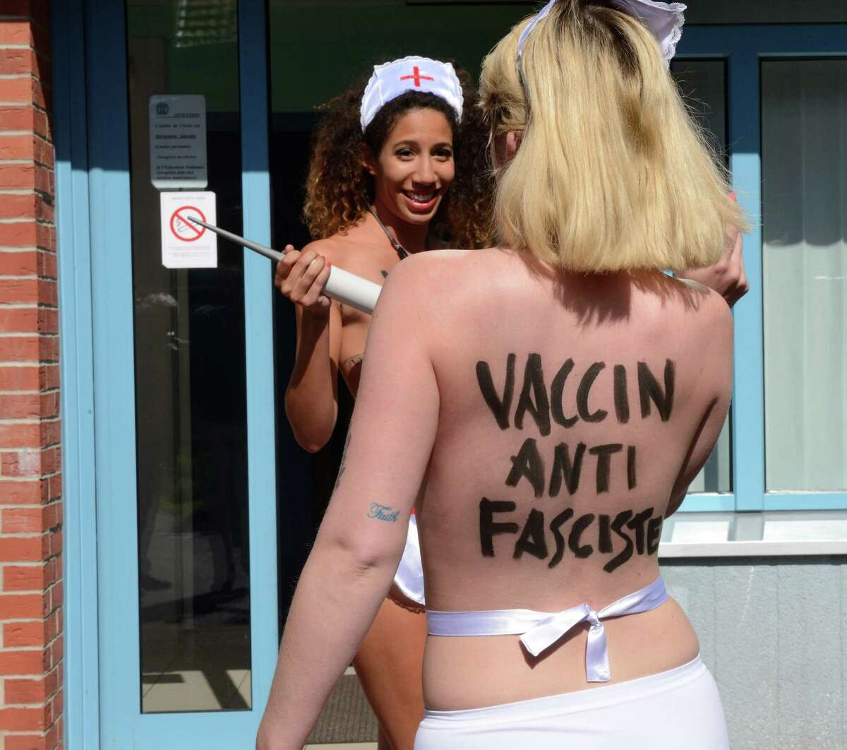 Femen activists take part in a protest after the vote of French far-right Front National (FN) party president in front of a polling station in Henin-Beaumont on May 25, 2014 during the vote for the European Parliament elections.