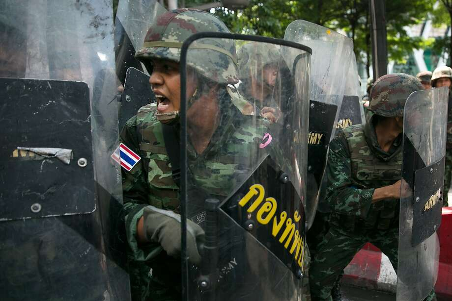 Thai military members, holding riot shields, confront demonstrators in Bangkok as protests grow in the wake of Thursday's military coup. Photo: Paula Bronstein, Getty Images