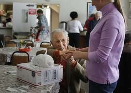 Julius Mansbach, 100, thanks Maria Ksenzova after she delivered the latest shipment of stamps, from Chronicle readers, before lunch at the Russian American Community Services center on Wednesday 21, 2014 in San Francisco, Calif.