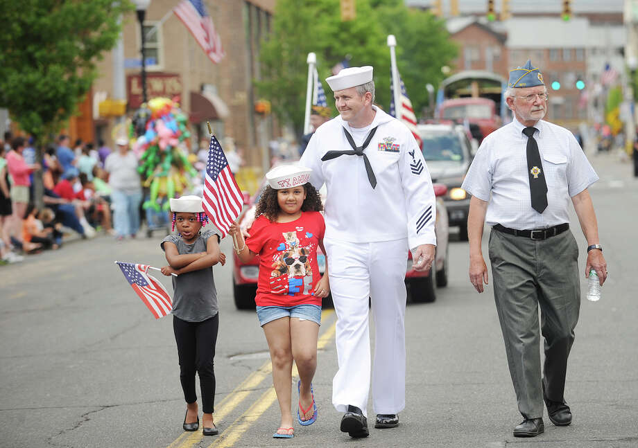 Builder 1st Class Thomas Henri marches with his arm around his granddaughter, Tianna Wheaton, 6, both of Ansonia, in the Memorial Day Parade on Main Street in Ansonia, Conn. on Sunday, May 25, 2014. at left is Alonna Ewell, 6, also of Ansonia. Photo: Brian A. Pounds / Connecticut Post