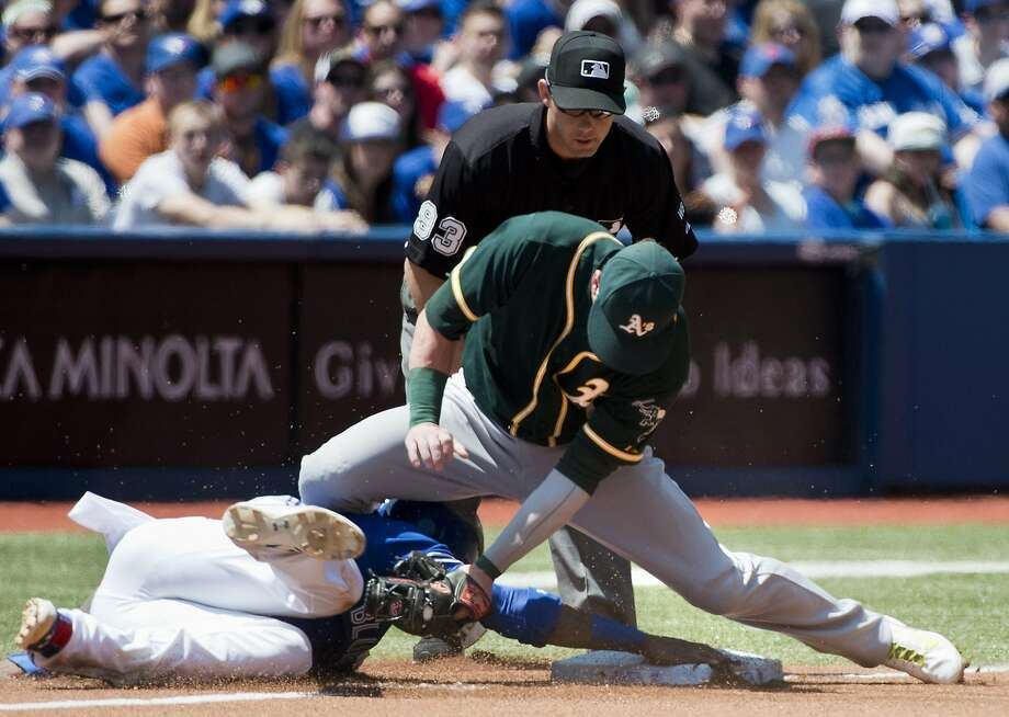 Toronto Blue Jays'  Jose Reyes, left, steals third base past Oakland Athletics third baseman baseman Josh Donaldson, right, during the first inning a baseball game on Sunday, May 25, 2014, in Toronto. (AP Photo/The Canadian Press, Nathan Denette) Photo: Nathan Denette, Associated Press