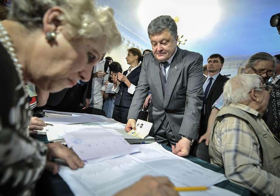 Ukrainian presidential hopeful Petro Poroshenko receives his ballots at a polling place in Kiev. Photo: Mykola Lazarenko, Associated Press