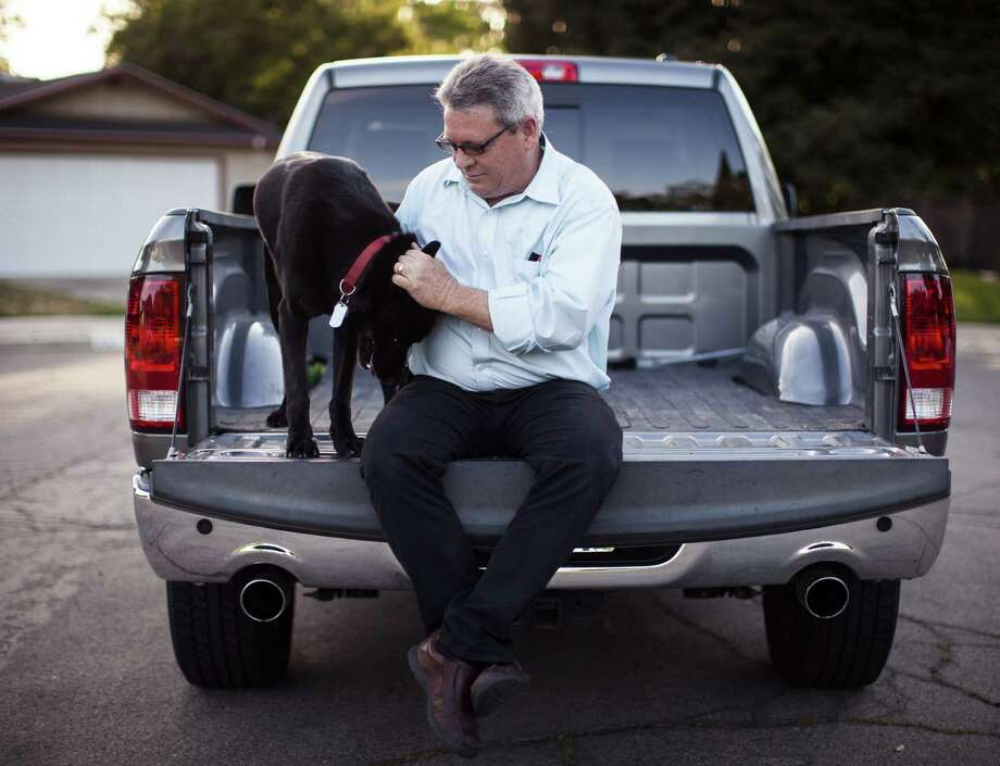 David Clayton sits with his dog on his pickup at his home in Fresno, Calif. Car dealerships and many manufacturers have opposed efforts to require the immediate repair of any recalled rental or used cars -- like the used Ram pickup Clayton nearly lost control of when the defective rear axle locked up. Photo: Max Whittaker / New York Times / NYTNS