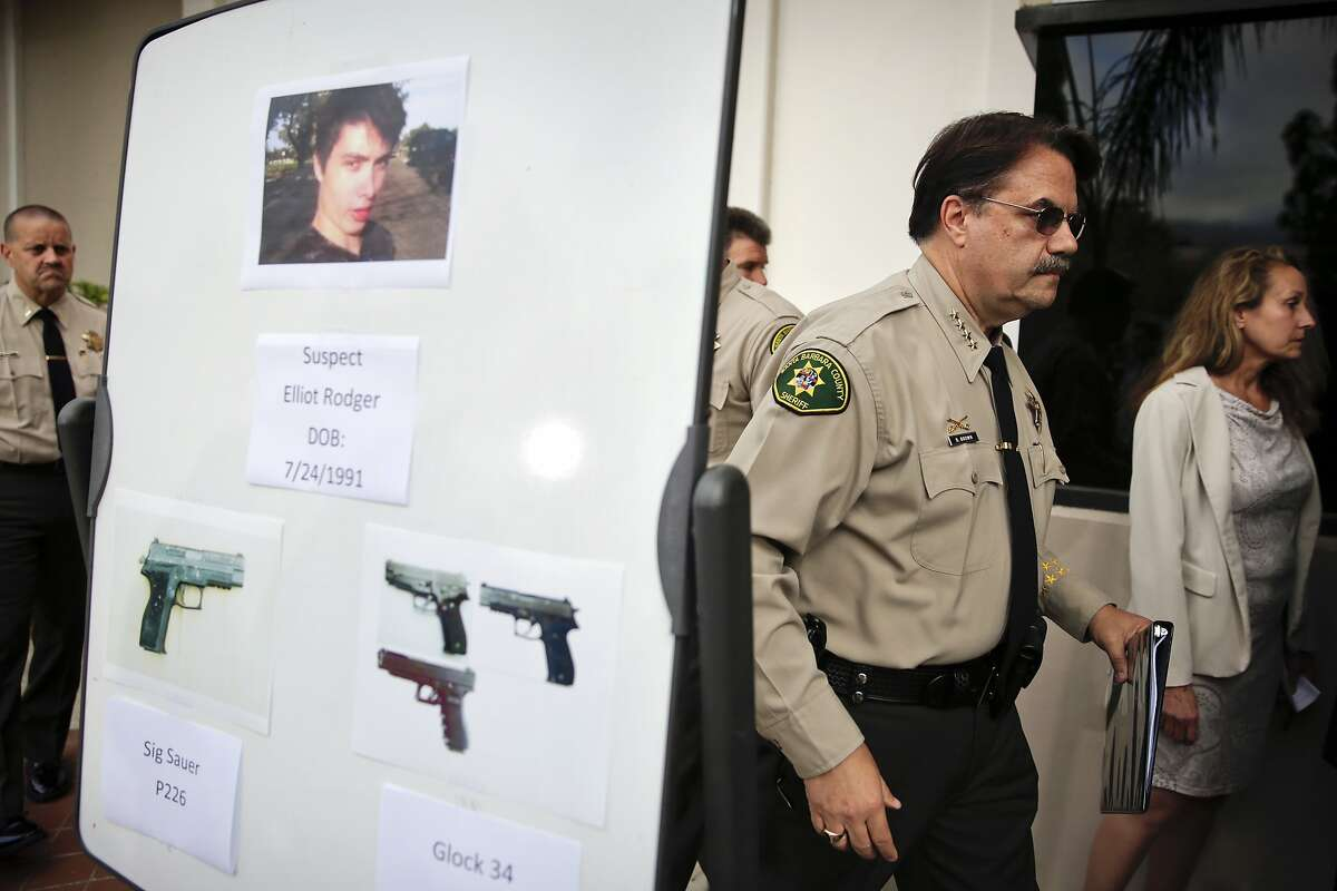 Santa Barbara County Sheriff Bill Brown, right, walks past a board showing the photos of suspected gunman Elliot Rodger and the weapons he used in Friday night's mass shooting that took place in Isla Vista, Calif., after a news conference on Saturday, May 24, 2014, in Santa Barbara, Calif. Sheriff's officials say Rodger, 22, went on a rampage near the University of California, Santa Barbara, stabbing three people to death at his apartment before shooting and killing three more in a crime spree through a nearby neighborhood. (AP Photo/Jae C. Hong)