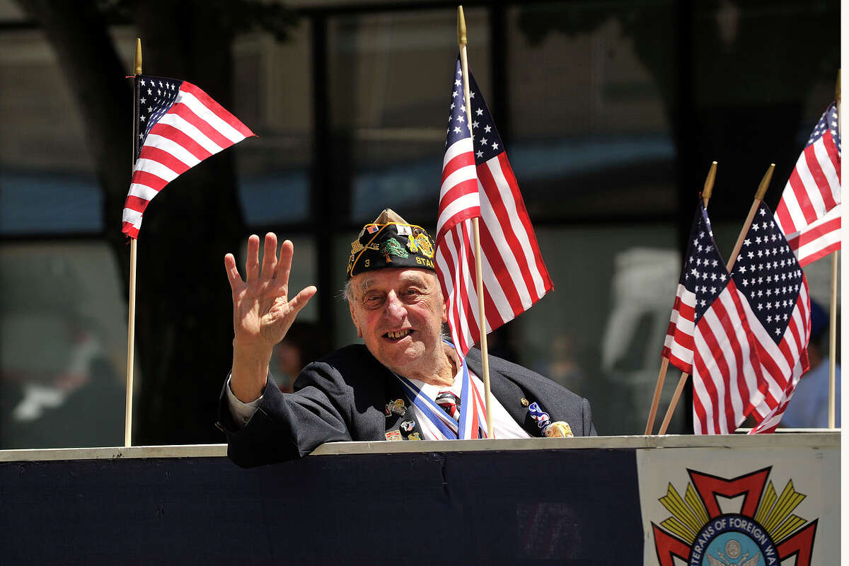 Korean War veteran Carmine Vaccaro waves from the back of a parade float during the Memorial Day parade in downtown Stamford, Conn., on Sunday, May 25, 2014.