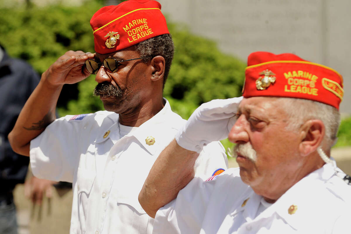 Richard Butler, left, and Pasquale Battinelli salute as the American flag is lowered to half-staff during the Memorial Day ceremony in downtown Stamford, Conn., on Sunday, May 25, 2014.