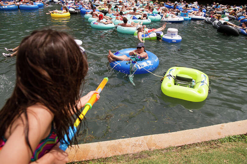 Christina Valle, has a water fight with Zoi Felan, 7, at Prince Solms Park on the Comal River Sunday