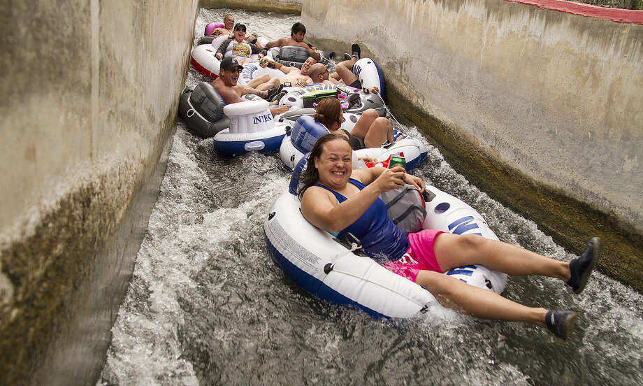 Armed with smiles and cans of beer, tubers braved intermittent rain as they came through the chute at Prince Solms Park. Photo: Alma E. Hernandez / For The San Antonio Express-News