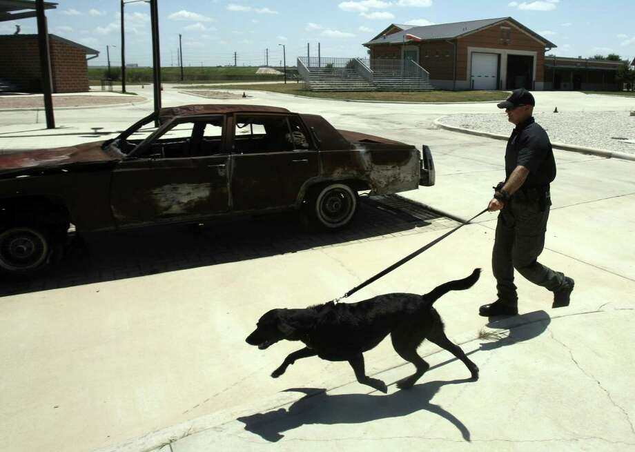 S.A. arson investigator Justin Davis and Kai have worked together for the past four years. Photo: Helen L. Montoya / San Antonio Express-News / SAN ANTONIO EXPRESS-NEWS
