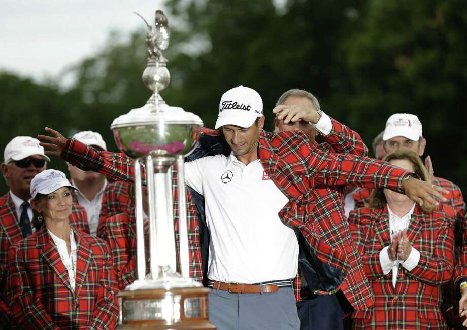 Adam Scott puts on the winner's jacket as he is presented the trophy after his victory at the Colonial. The world's No. 1 player became the first to win all four PGA Tour events in Texas. Photo: LM Otero / Associated Press / AP