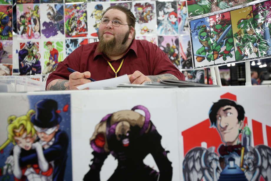 Johnny Segura III of Lake Charles, La., creates and sells fan art at conventions using pens, pencils and design programs. The paper quilt he displayed Sunday at the George R. Brown Convention Center features more than 150 prints. Photo: Mayra Beltran, Staff / © 2014 Houston Chronicle