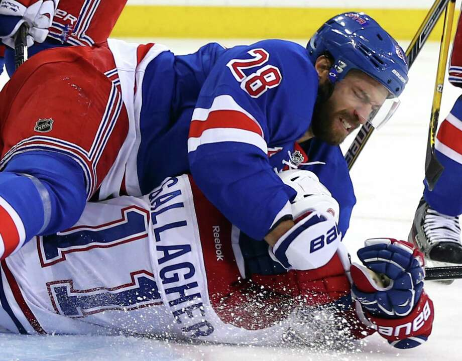 The Rangers' Dominic Moore (top) throws Brendan Gallagher of the Canadiens to the ice during New York's 3-2 overtime victory Sunday. The Rangers have a 3-1 lead in the East finals. Photo: Elsa / Getty Images / 2014 Getty Images