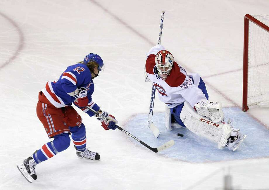 New York Rangers' Carl Hagelin, left, scores past Montreal Canadiens goalie Dustin Tokarski during the first period of Game 4 of the NHL hockey Stanley Cup playoffs Eastern Conference finals, Sunday, May 25, 2014, in New York. (AP Photo/Seth Wenig) ORG XMIT: MSG301 Photo: Seth Wenig / AP