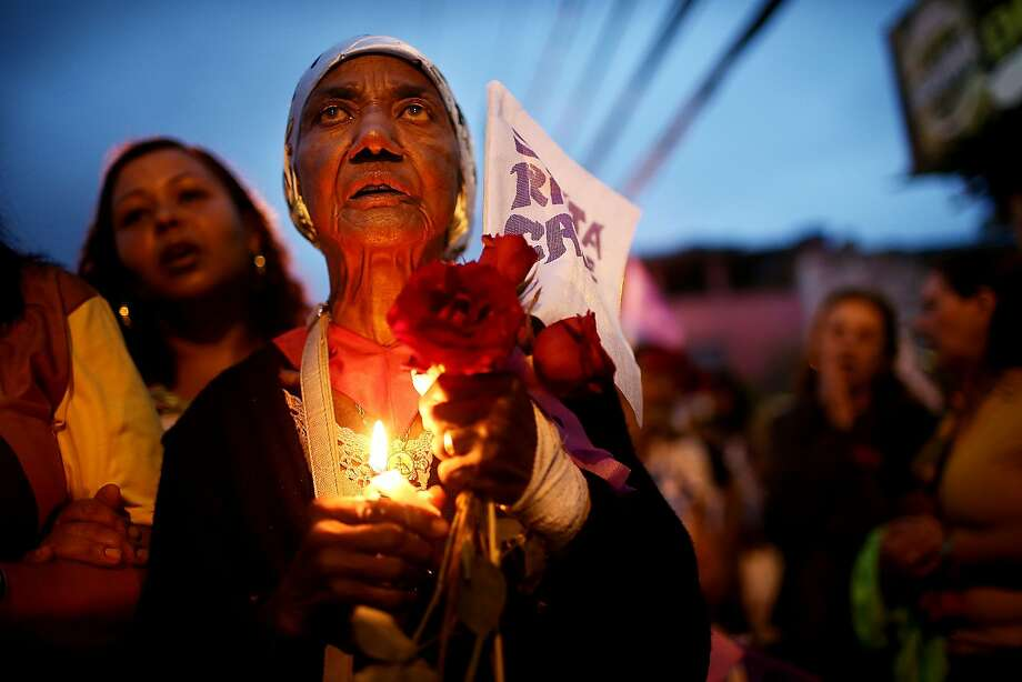 RIO DE JANEIRO, BRAZIL - MAY 25:  Alcemira da Silva Muniz (2nd L) carries a candle while marching in a Catholic procession honoring Saint Rita, the patron saint of the impossible, on May 25, 2014 in Rio de Janeiro, Brazil. The 2014 FIFA World Cup kicks off June 12 in Brazil, the largest country of Catholics in the world.  (Photo by Mario Tama/Getty Images) Photo: Mario Tama, Getty Images